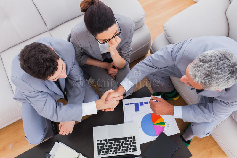 Business people sitting on sofa shaking hands during meeting. At office stock photo