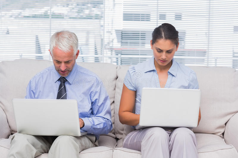 Download Business People Sitting On Sofa Using Their Laptops Stock Image - Image: 32234223