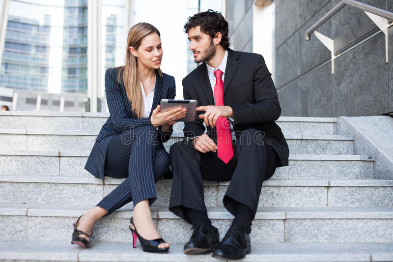 Business people sitting on a staircase royalty free stock image