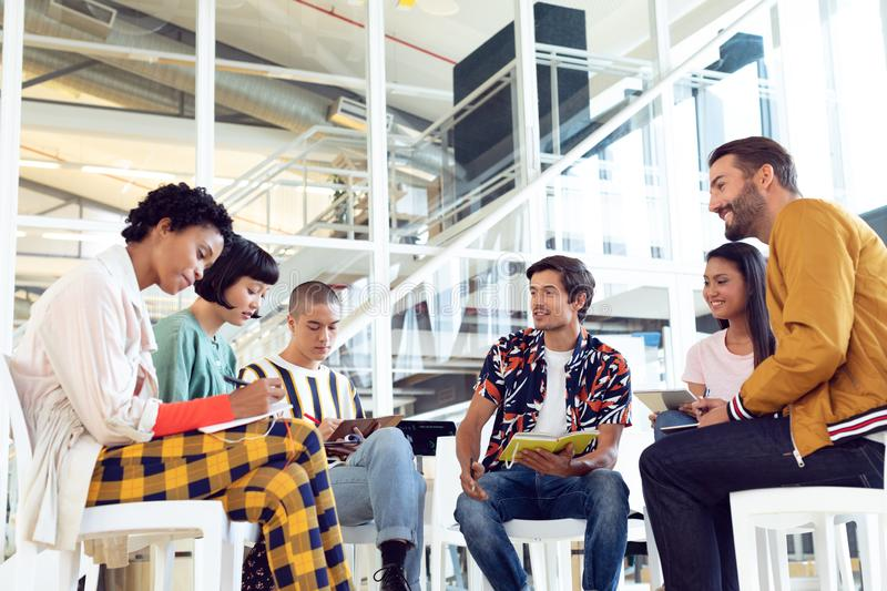 Business people sitting together and having group discussion in office. Low angle view of diverse Business people sitting together and having group discussion in royalty free stock images
