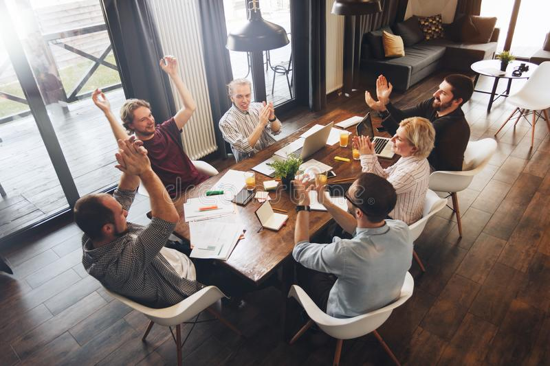 Business people sitting at a wooden table using laptops and paper document and applauding a successful concluded deal. Teamwork c. Oncept. Mke a deal royalty free stock photos