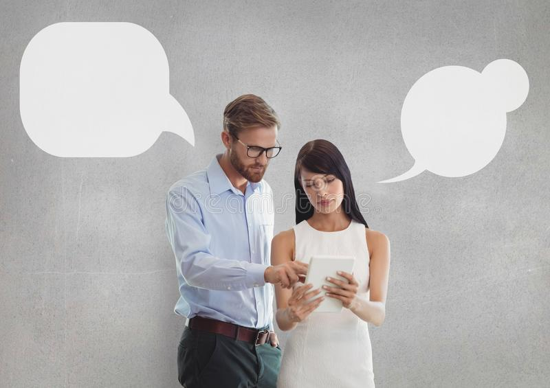 Business people with speech bubbles looking at a tablet against grey background stock photo