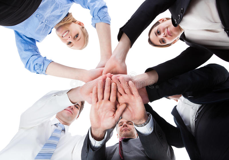 Business people stacking hands. Low Angle View Of Businesspeople Stacking Hands Together Over White Background royalty free stock image