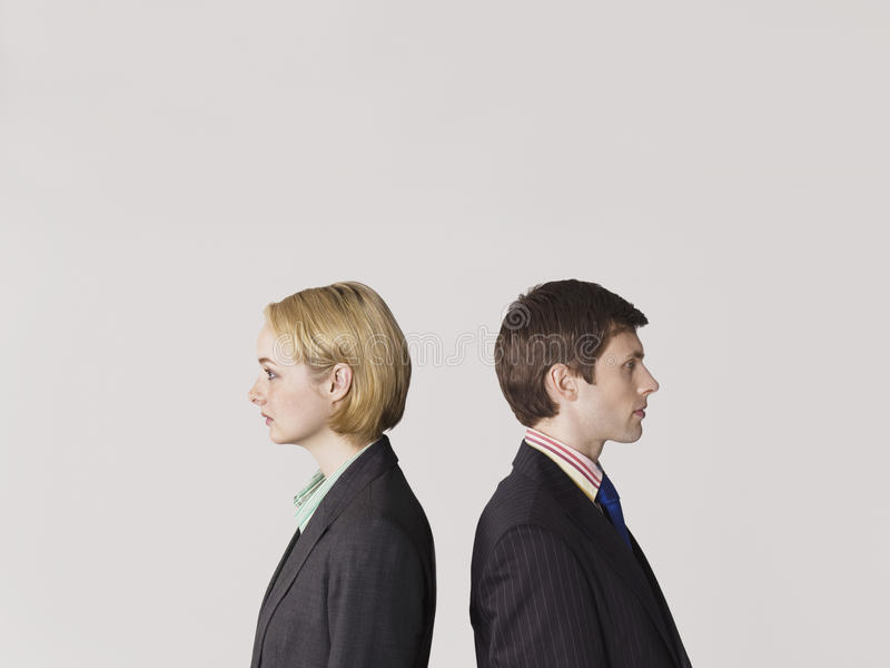 Business people Standing Back To Back On Gray Background royalty free stock photography