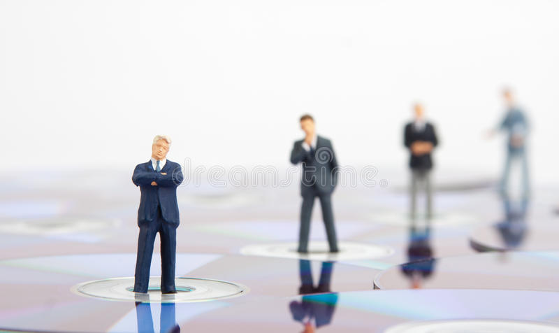 Business people standing on computer CDs royalty free stock image