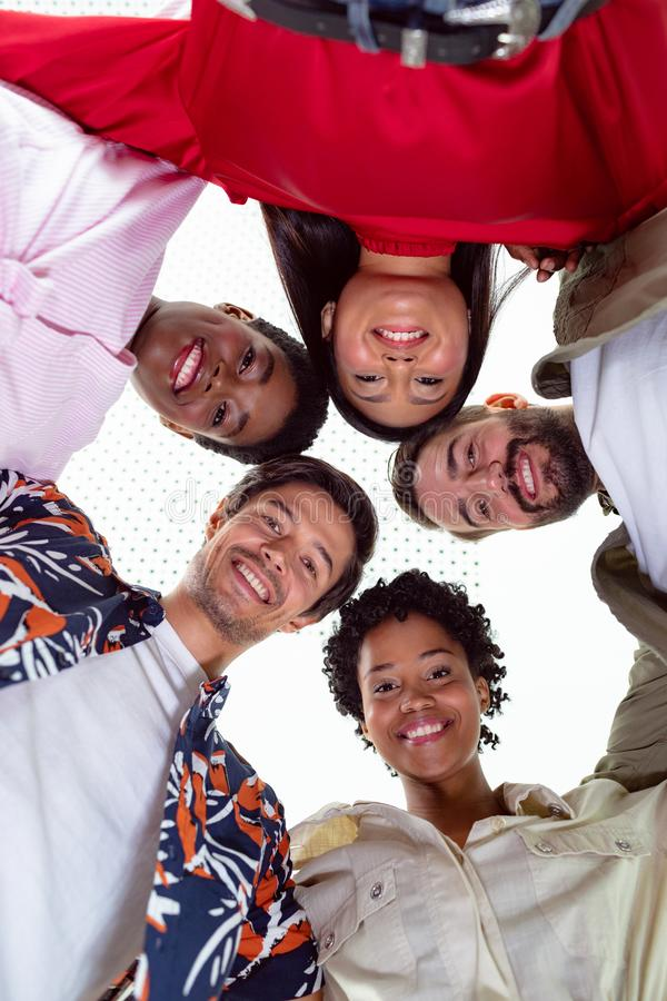 Business people standing in huddle in a modern office. Low angle view of team of diverse business people standing in huddle in a modern office royalty free stock images