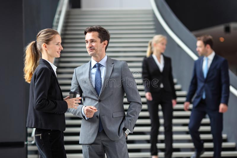 Business people standing in office lobby stock photos