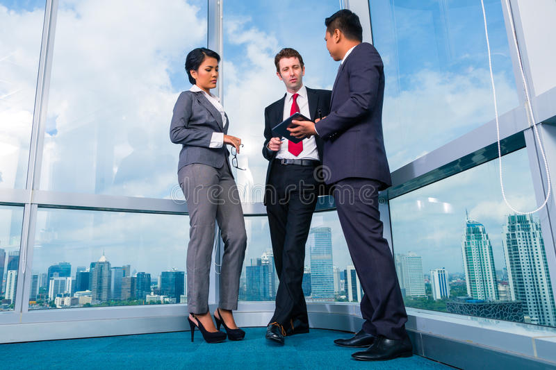 Business people standing at office window working royalty free stock photography