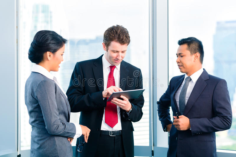 Business people standing at office window working stock photography