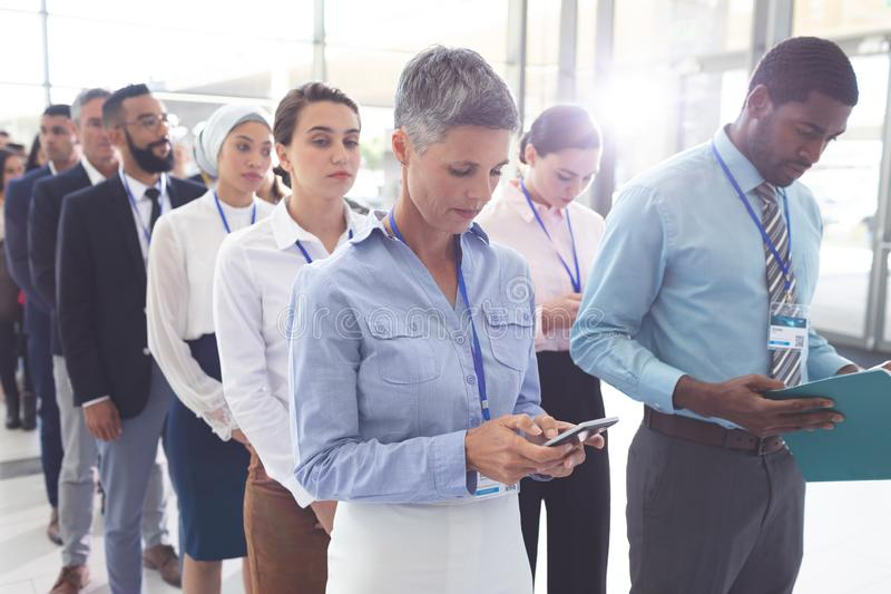 Business people standing in queue in lobby and looking files and their mobile phone stock images