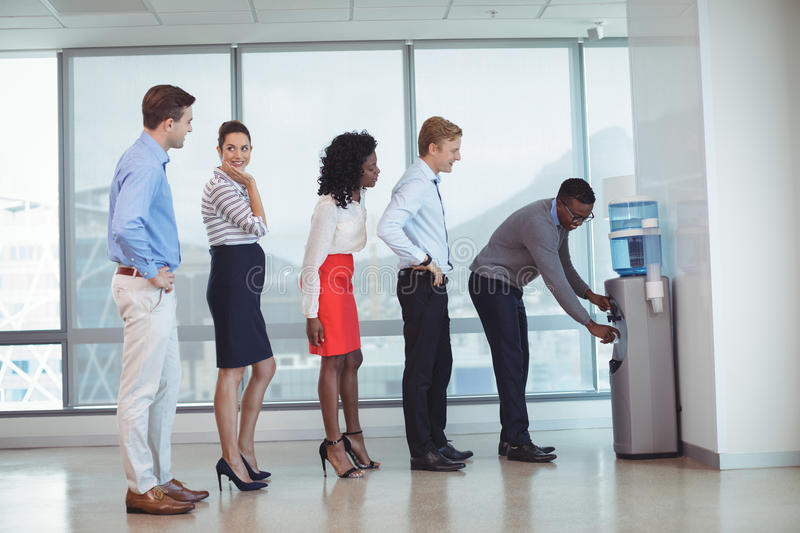 Business people standing by water cooler at office. Business people standing in line by water cooler at office royalty free stock photos