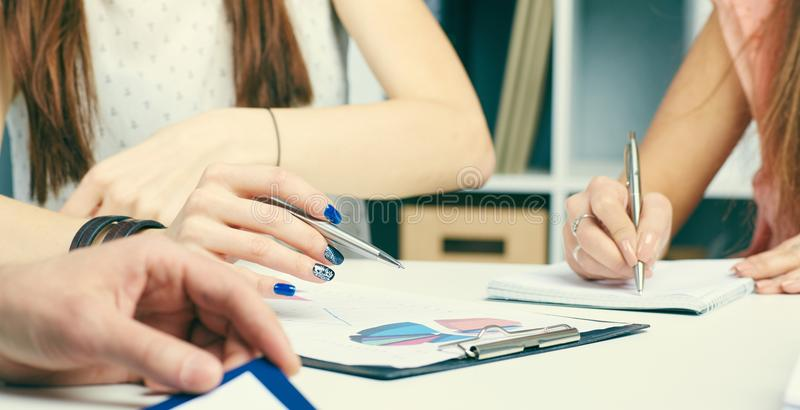 Mid section of a business woman with clipboard pointing pen to chart at office. royalty free stock photography