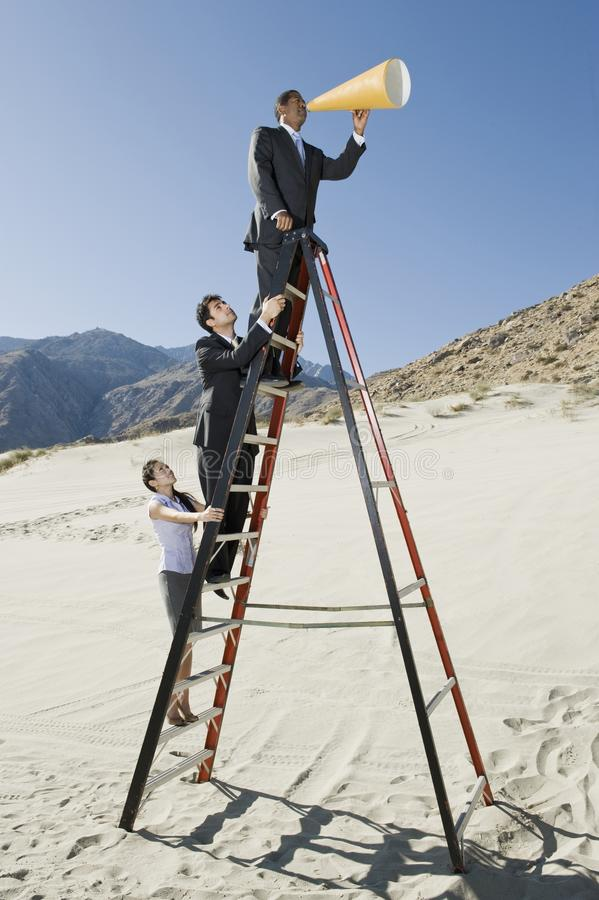 Business People on Stepladder Using Megaphone in Desert. Side view of businessman using megaphone with colleagues standing on ladder in desert stock photo