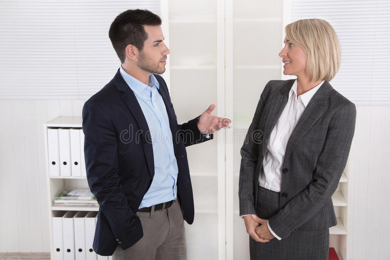 Business people in suit and dress talking together: small talk. Business people in suit and dress talking together: small talk in a professional meeting stock photos