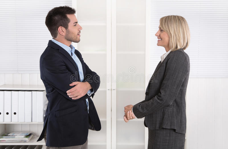 Business people in suit and dress talking together: small talk. Business people in suit and dress talking together: small talk in a professional meeting royalty free stock photos