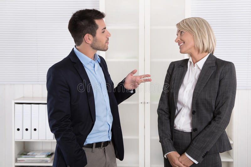Business people in suit and dress talking together: small talk. Business people in suit and dress talking together: small talk in a professional meeting stock images