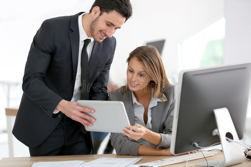 Business people with tablet at office. Business people in office working on tablet stock photo