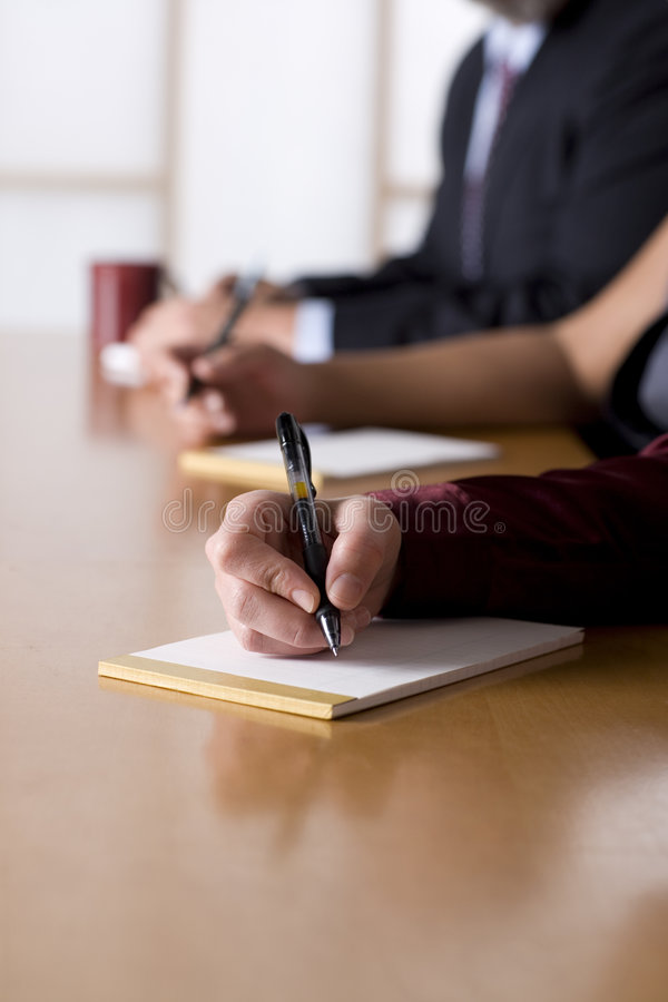 Business people taking notes in a meeting royalty free stock photos