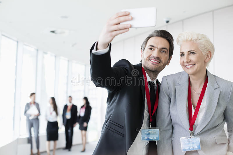 Business people taking selfie in convention center with colleagues walking in background stock image