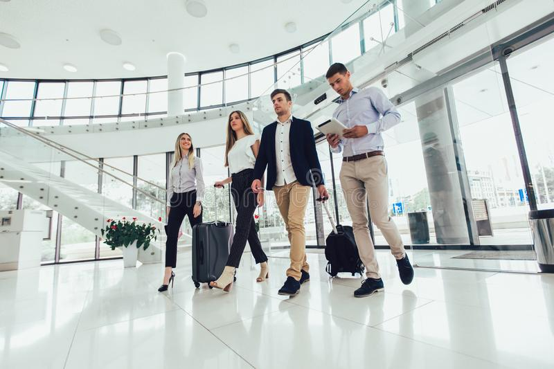 Business people talk and walk together with digital tablet tablet and luggage stock photos