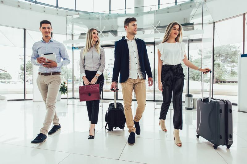Young business people talk and walk together with digital tablet tablet and luggage royalty free stock image