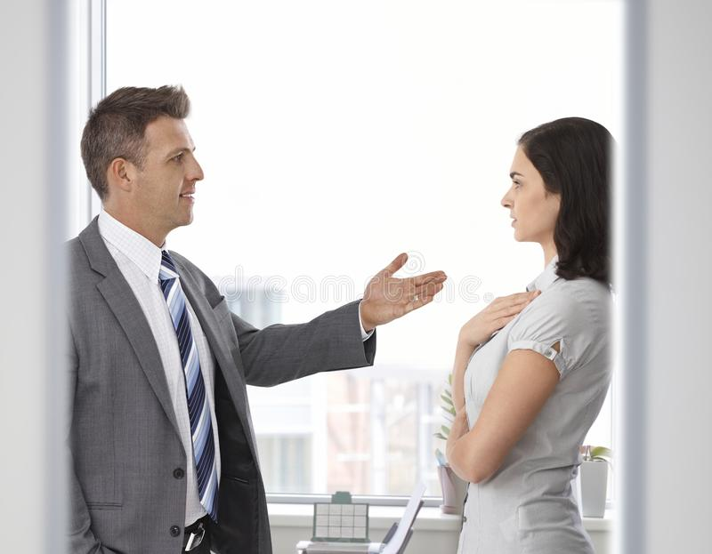 Business people talking front of window at office. Standing, looking at each other. Suit, explanation, gesturing royalty free stock photo