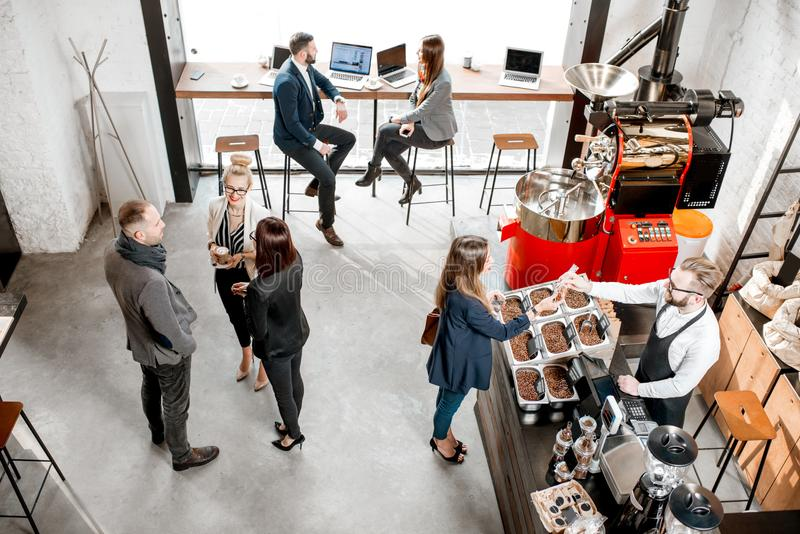 Business people in the cafe. Business people talking and having fun durnig a coffee time in the modern cafe interior. Wide view from above stock photography