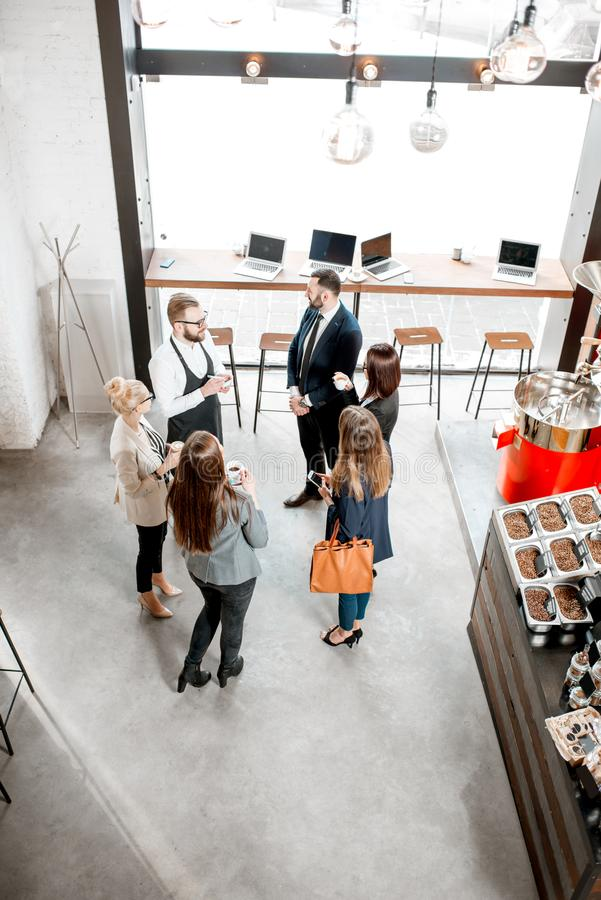 Business people in the cafe. Business people talking and having fun durnig a coffee time in the modern cafe interior. Wide view from above stock image