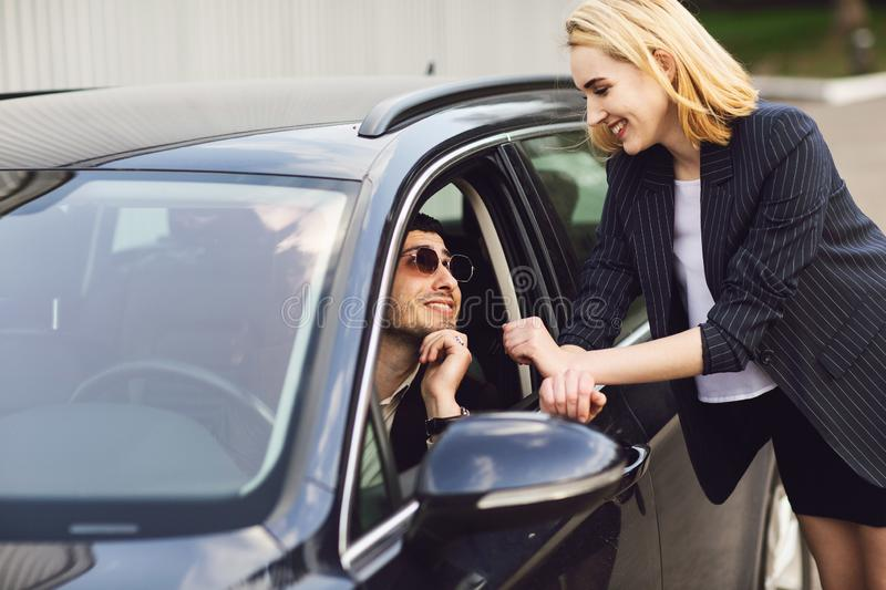 Business people talking near car park. The man in the glasses is sitting in the car, the woman stands next to him stock photo