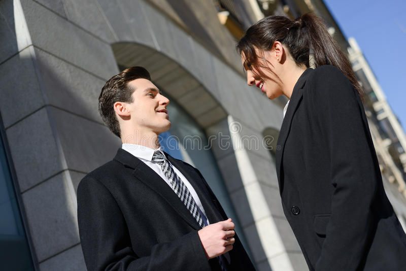 Business people talking outside of company building. Couple work royalty free stock photography