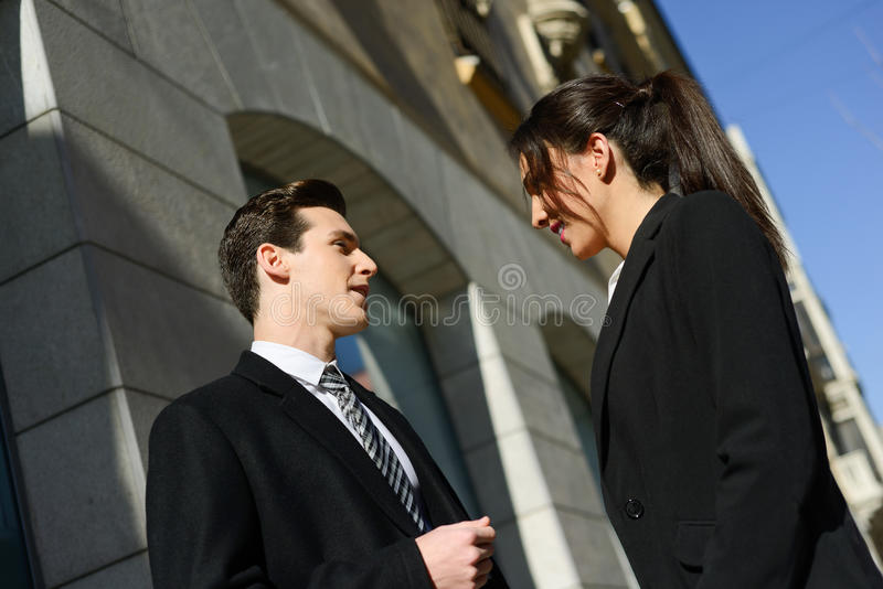 Business people talking outside of company building. Couple work stock photo
