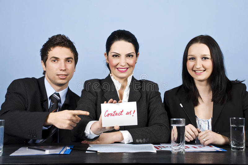 Business people team with contact us message. Group of three business people teamwork sitting in a line at table smiling and looking for you, a businesswoman royalty free stock images