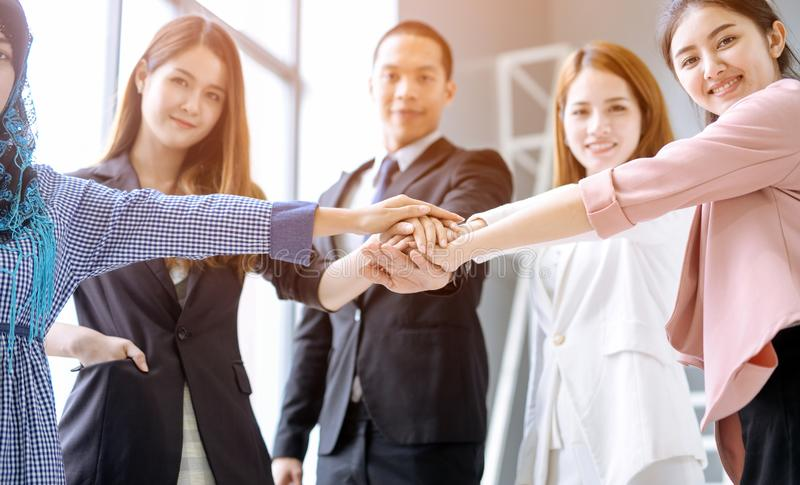 Business people in team stack hands together as unity and teamwork in office. young Asian businessman and group togetherness colla royalty free stock photography