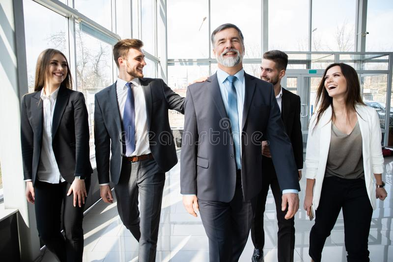 Business People Team Walking In Modern Office, Confident Businessmen And Businesswomen With Mature Leader In Foreground. stock photo