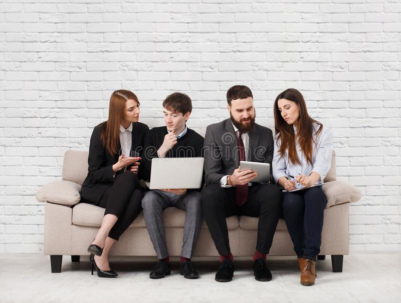 Business people teambuilding. Team on couch, partners working together royalty free stock image