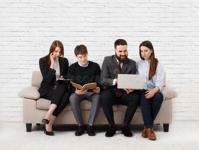 Business people teambuilding. Team on couch, partners working together royalty free stock photography