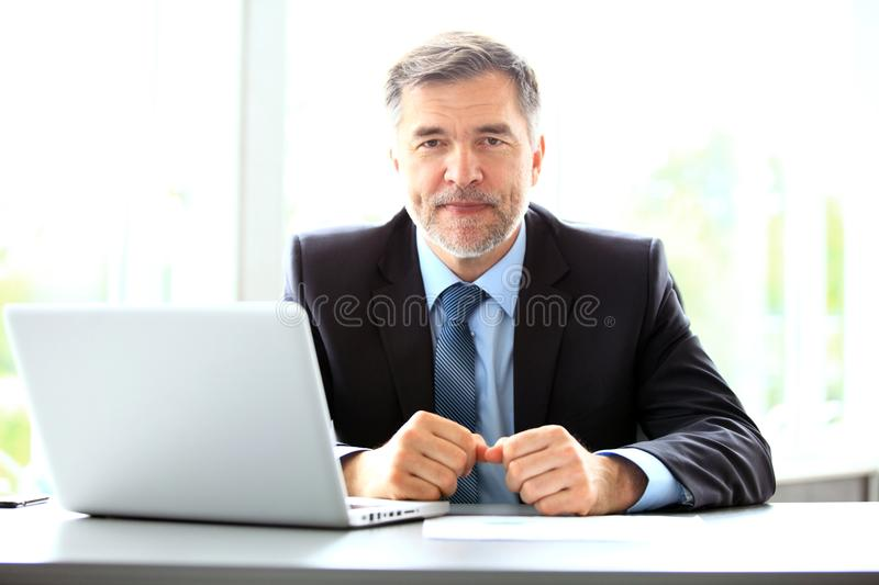 Business, people and technology concept - happy smiling businessman with laptop computer office royalty free stock photo