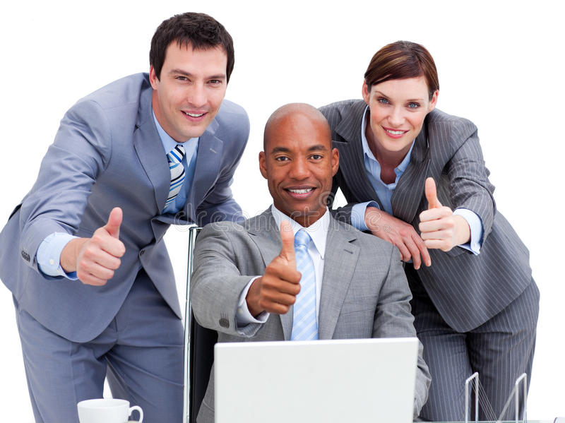 Business people with thumbs up looking at a laptop stock image
