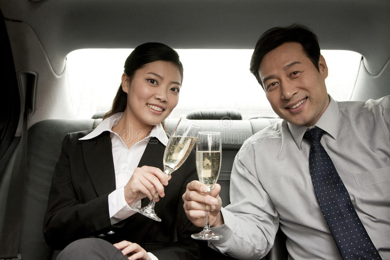 Business people toasting champagne back of car stock photography