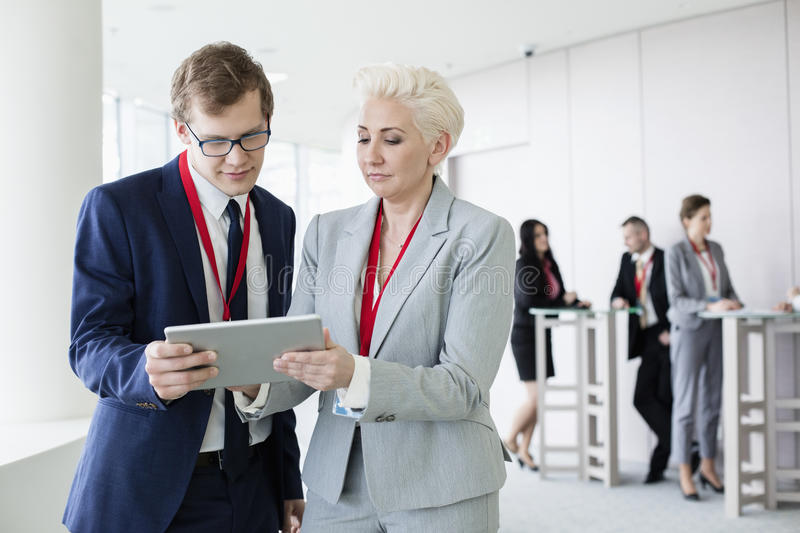 Business people using digital tablet in convention center royalty free stock photography