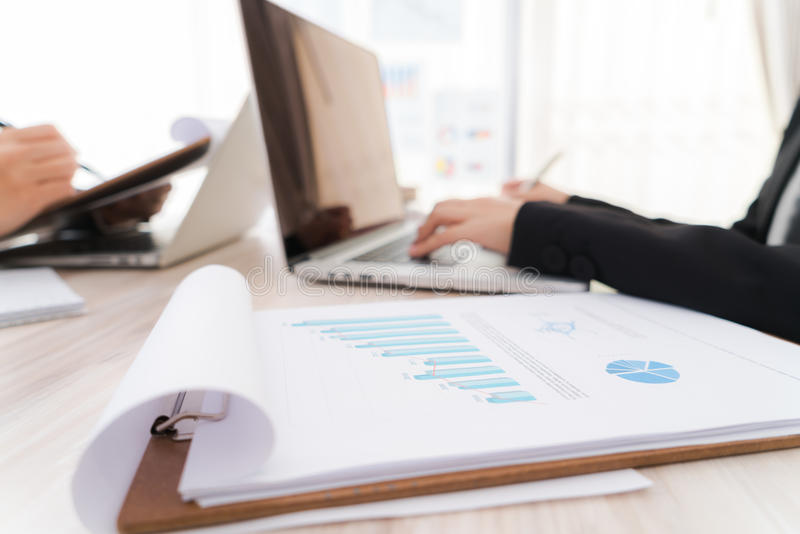 Business people using laptop and Financial charts at meeting o stock photo