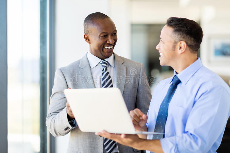 Business people using laptop. Multiracial business people using laptop in modern office stock image