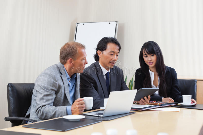 Business people using tablet in meeting stock photography