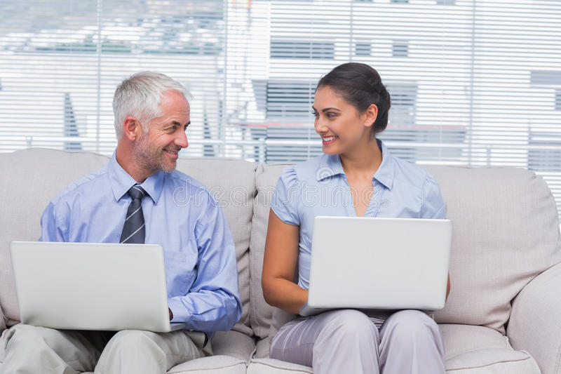 Download Business People Using Their Laptops And Smiling At Each Other Stock Photo - Image: 31668708