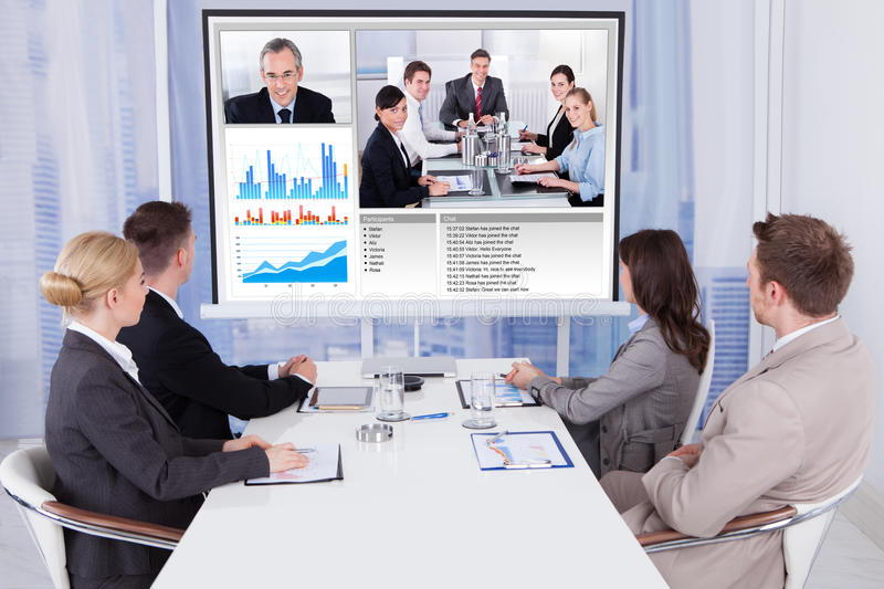 Business people in video conference at table. Group of business people attending video conference at table in office stock image