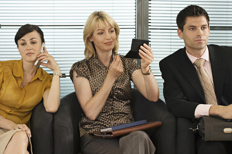 Business people waiting in office reception, woman using mobile phone, second woman applying make-up royalty free stock image
