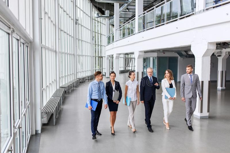 Business people walking along office building royalty free stock photography