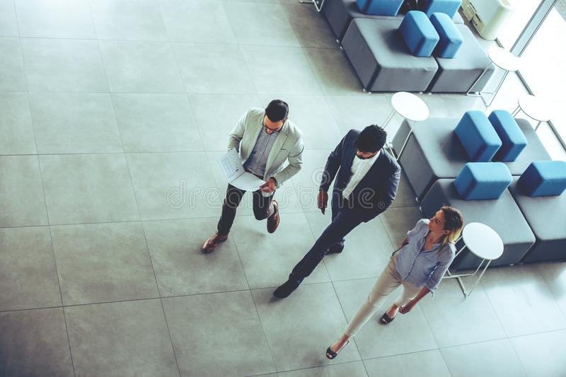 Business people walking in business building and having conversa stock image
