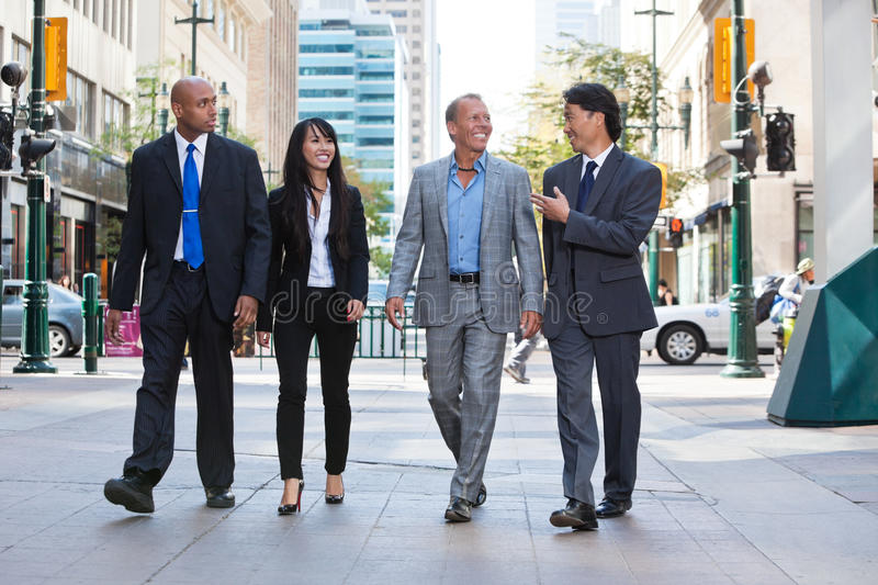 Business people walking together on street. Group of happy business people walking together on street stock photography