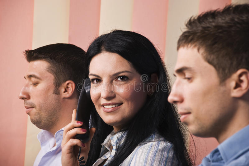Business people with woman calling by phone. Close up of business people at work,men standing in profile and looking down reading and the woman facing camera stock photos